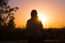Silhouette of a beautiful Yoga woman on sunrise and rays of light surrounding her
