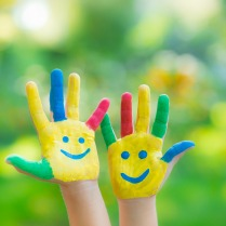 Smiley hands against green blurred background. Children having fun in spring outdoors. Ecology concept