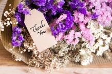 Bouquet of dried flowers with thank you card on the wooden table