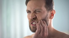 Man feeling strong tooth ache, strong dental pain, pulp inflammation, decay